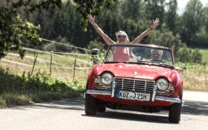 Ein Oldtimer Cabrio Triumph. Die Beifahrerin streckt die Hände vor Freude zum Himmel